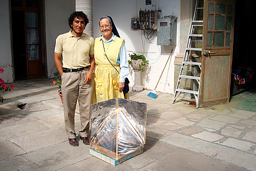 F and Madre Lourdes stand behind the solar cooker Madre Lourdes loves to use and is so proud of.